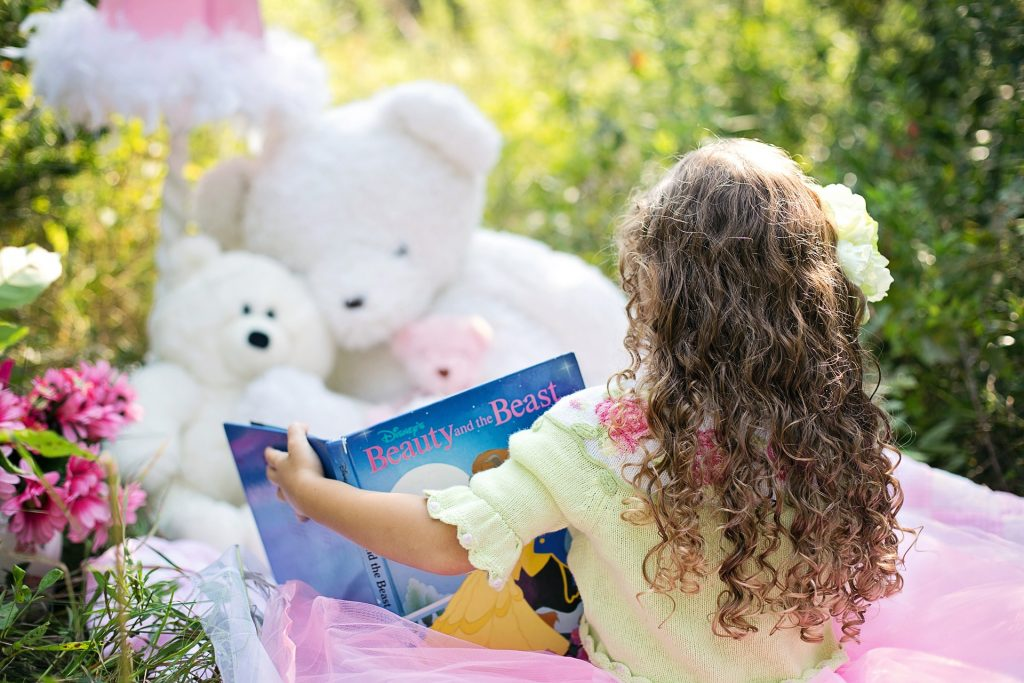 little girl reading in a comfortable environment created by her; reading to teddy bears