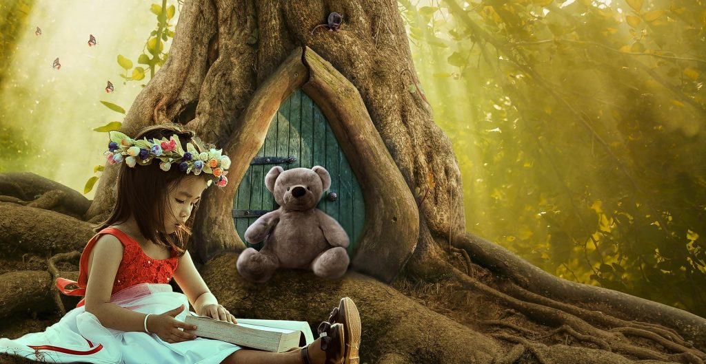 young girl reading to teddy bear