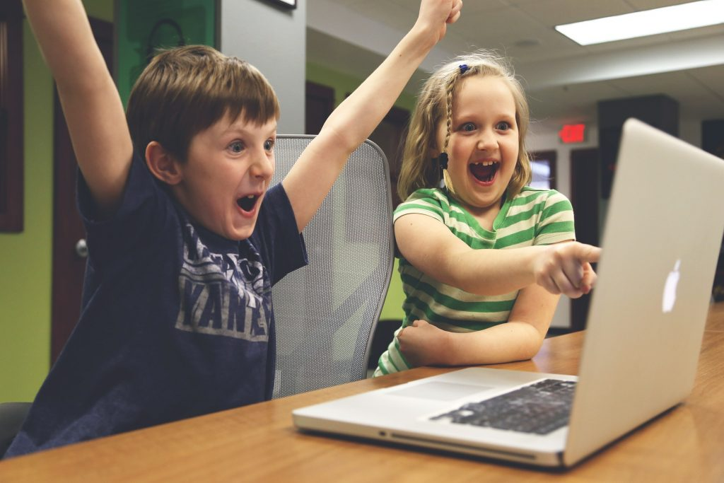 children celebrating while playing video games