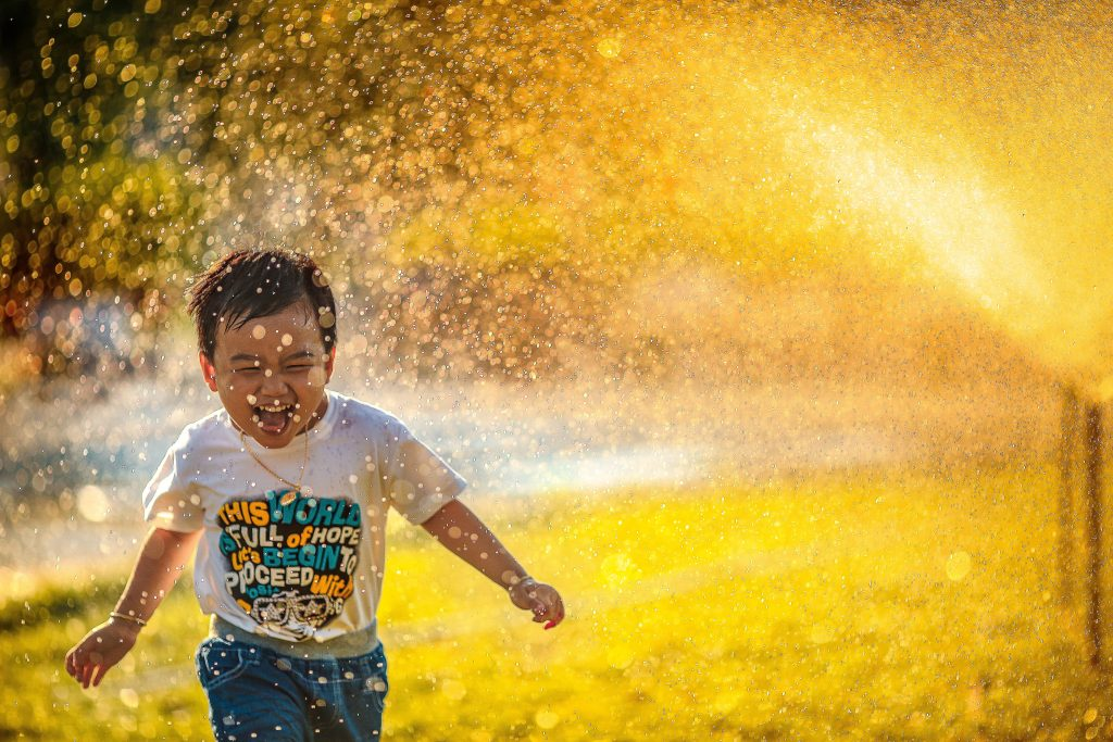 young boy running through a sprinkler; a happy picture displayed in both tone and mood