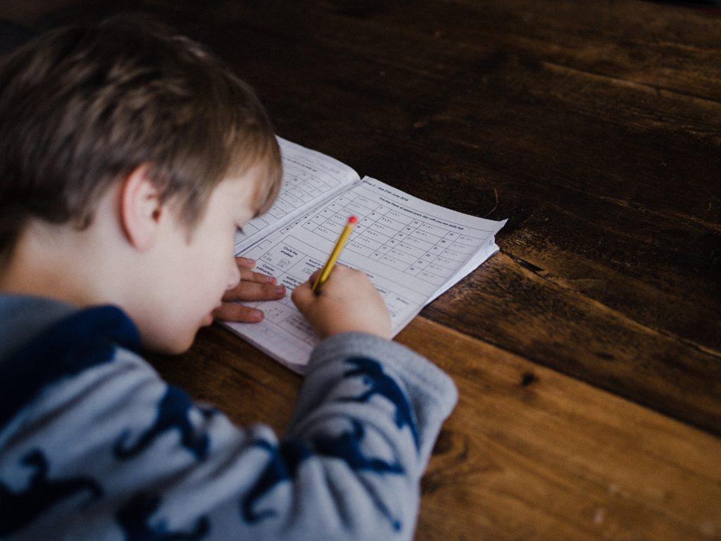 The Ultimate List of free Homeschooling Resources; boy being homeschooled;